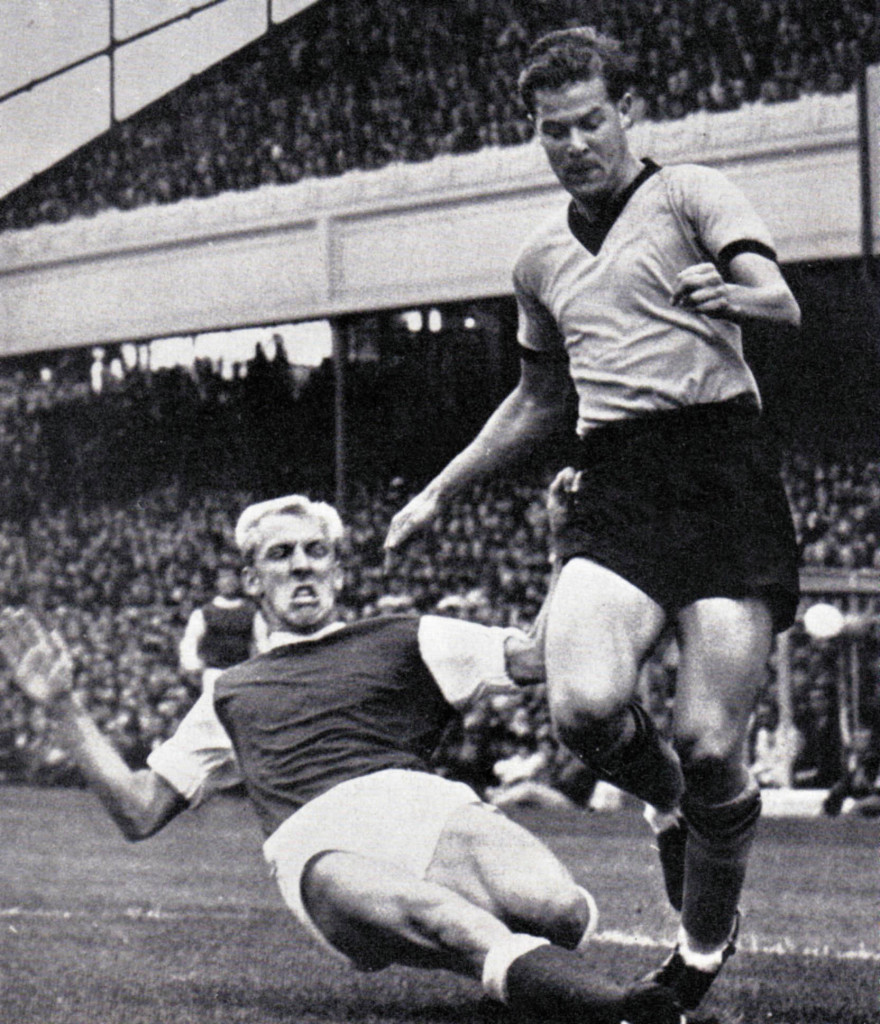 Ted Farmer is tackled by Ian Ure during his appearance against Billy Wright's Arsenal on the opening day of 1963-64.